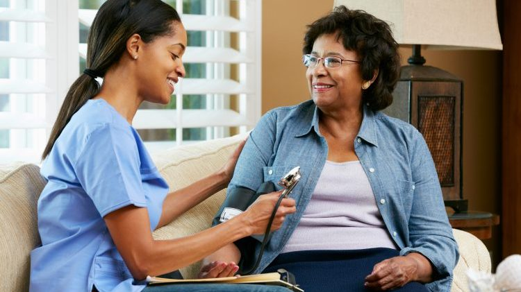 Nurse with lone worker alarms Visiting Senior Female Patient At Home