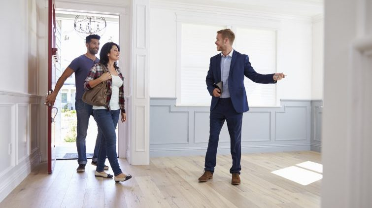 Lone Working Realtor Showing Couple Around New Home
