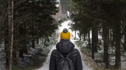 alone young woman in black down jacket and yellow knitted hat with rucksack in the depth of the black forest during cold winter day in finland